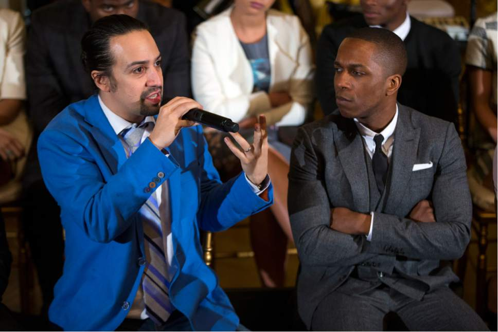 "Actor Leslie Odom Jr., right, listens as actor Lin-Manuel Miranda speaks during an event with the cast of the Broadway play ""Hamilton"" in the East Room of the White House, on Monday, March 14, 2016, in Washington. (AP Photo/Evan Vucci)"
