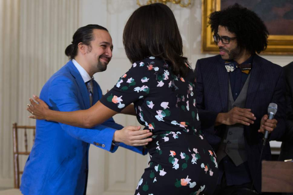 "Actor Daveed Diggs, right, watches as actor Lin-Manuel Miranda, left, hugs First Lady Michelle Obama during an event with the cast of the Broadway play ""Hamilton"" in the State Dining Room of the White House, on Monday, March 14, 2016, in Washington. (AP Photo/Evan Vucci)"