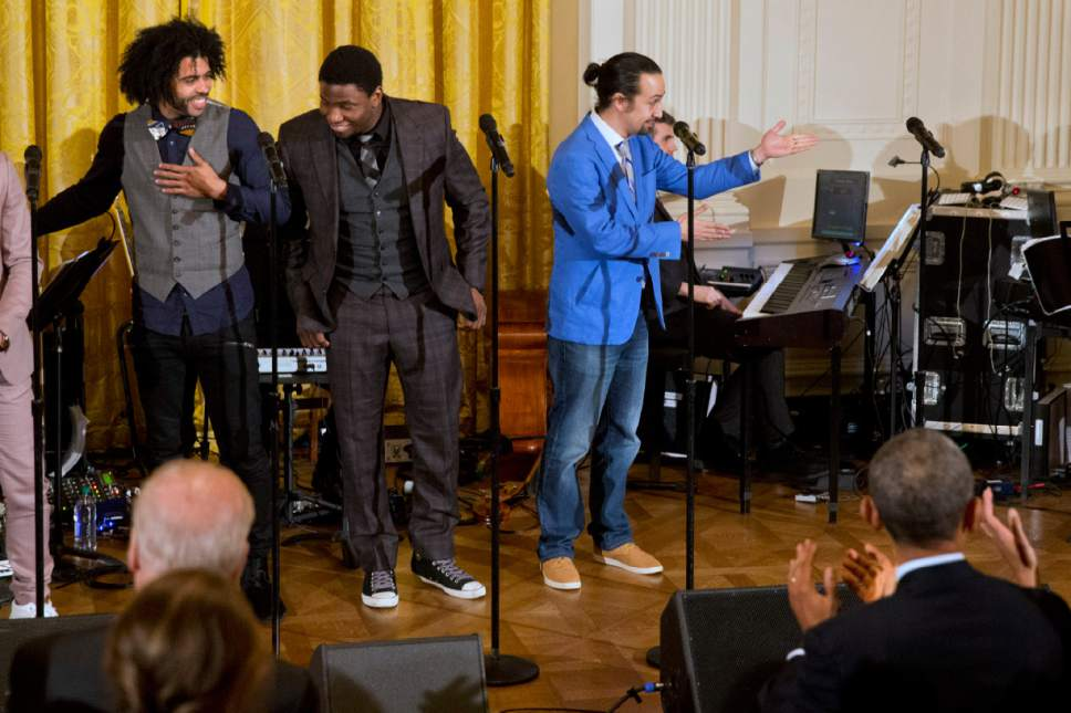 "As President Barack Obama applauds in the foreground at right, actor Lin-Manuel Miranda, right, gestures to the rest of the cast after singing ""Alexander Hamilton"" from the Broadway play ""Hamilton"" in the East Room of the White House, in Washington, Monday, March 14, 2016. At left are actors Daveed Diggs and Okieriete Onaodowan. (AP Photo/Jacquelyn Martin)"