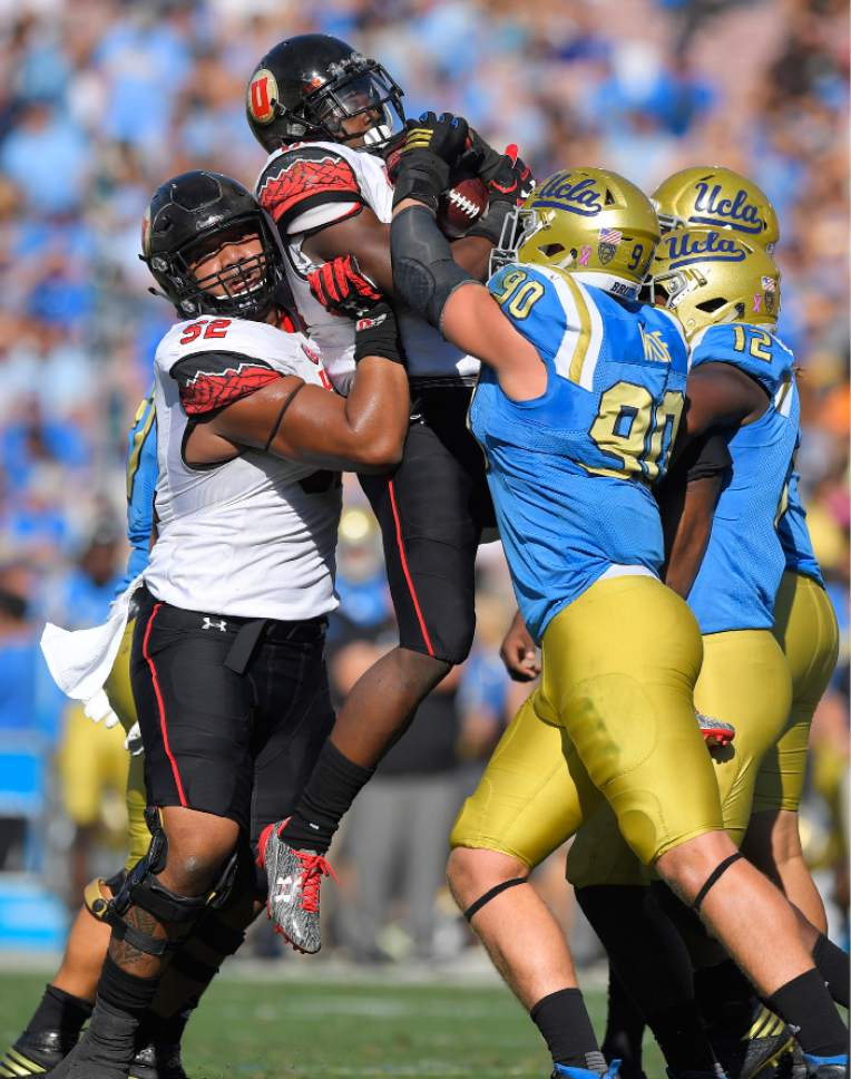 UCLA defensive lineman Rick Wade (90) and linebacker Jayon Brown (12) try to stop Utah running back Joe Williams, second from left, as offensive tackle Sam Tevi supports him during the first half of an NCAA college football game, Saturday, Oct. 22, 2016, in Pasadena, Calif. (AP Photo/Mark J. Terrill)