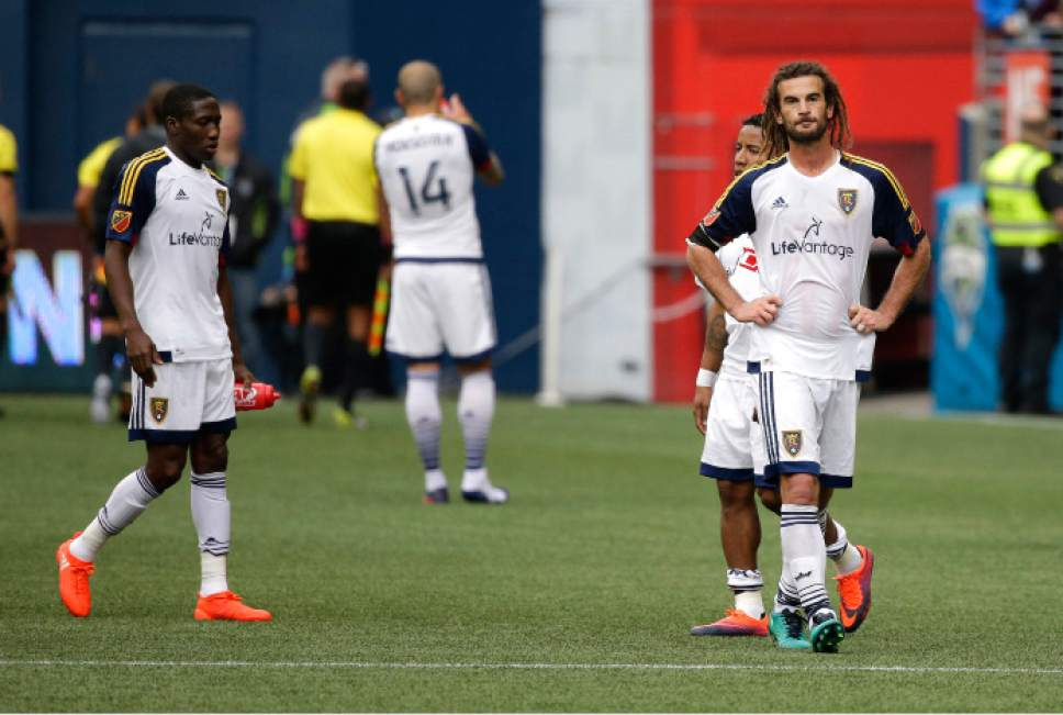 Real Salt Lake players, including midfielder Kyle Beckerman, right, stand on the pitch after an MLS soccer match against the Seattle Sounders, Sunday, Oct. 23, 2016, in Seattle. The Sounders defeated Real Salt Lake 2-1, clinching a spot in the MLS playoffs. (AP Photo/Ted S. Warren)