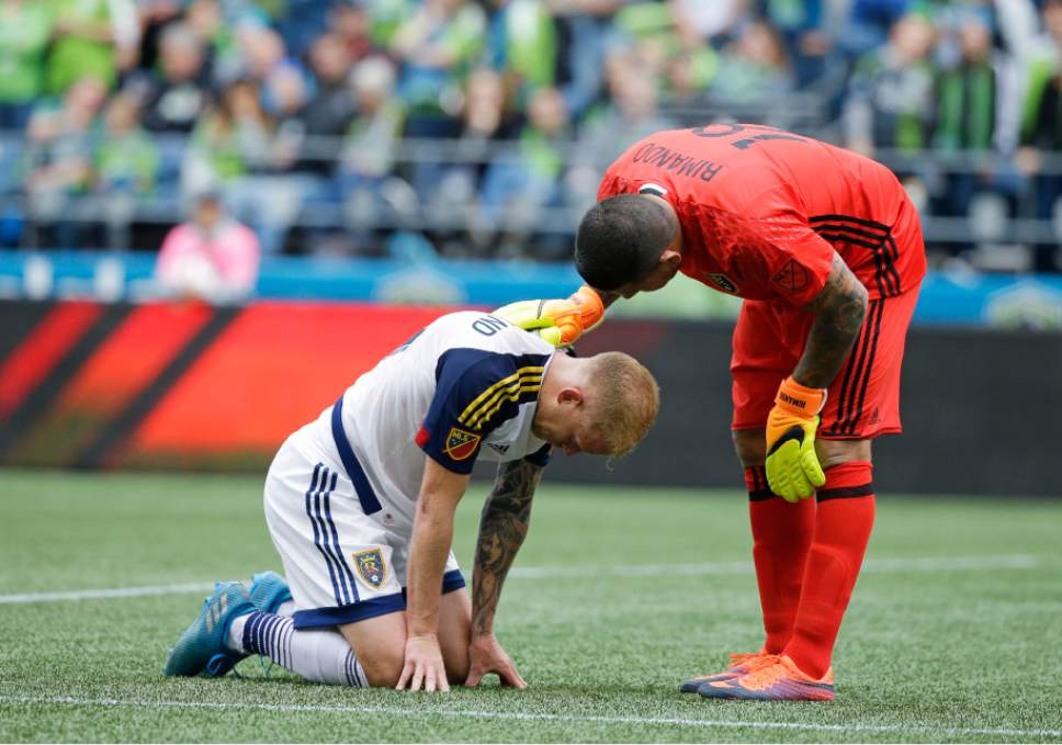 Real Salt Lake goalkeeper Nick Rimando, right, talks with midfielder Luke Mulholland after Mullholland went down with an injury in the first half of an MLS soccer match against the Seattle Sounders, Sunday, Oct. 23, 2016, in Seattle. (AP Photo/Ted S. Warren)