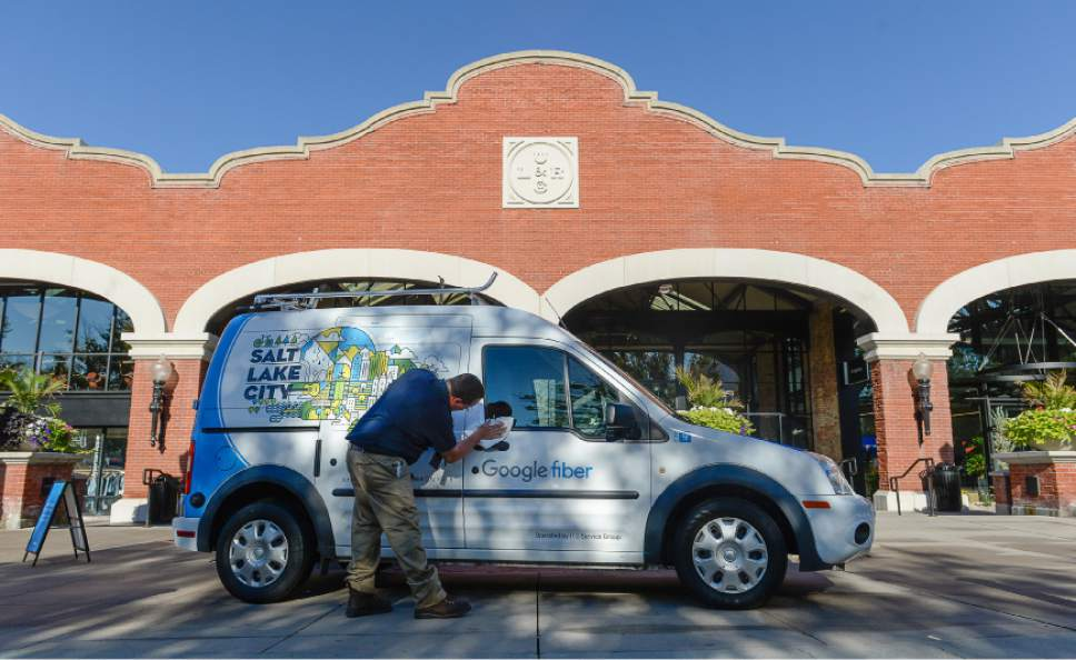 Francisco Kjolseth | The Salt Lake Tribune Job Chadwick wipes down a Google car prior to the start of an announcement by Google Fiber during a grand opening-type event at their offices in Trolley Square -- referred to as Fiber Space -- on Wednesday, Aug. 23, 2016.