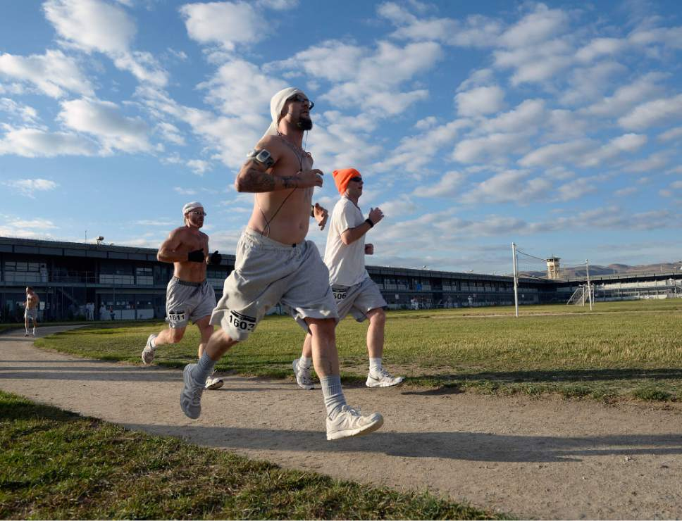 Al Hartmann  |  The Salt Lake Tribune Inmates at the Utah State Prison-Draper run the enclosed excercise yard-track at the start of the Draper Invitational Marathon, Half-Marathon and 10K races Tuesday morning October 25. A group of three frontrunners stick together for the first part of the race. 110 times around the track for the full marathon.