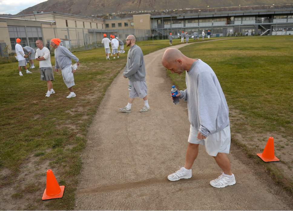 Al Hartmann  |  The Salt Lake Tribune Inmate at Utah State Prison-Draper scratches a starting line in the track to mark the starting line for Tuesday October 25's  Draper Invititational Marathon, half marathon and 10K run in the excercise field-track.