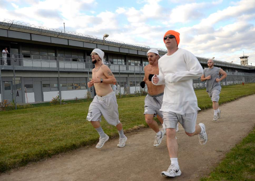 Al Hartmann  |  The Salt Lake Tribune Inmates at the Utah State Prison-Draper run the enclosed excercise yard-track at the start of the Draper Invitational Marathon, Half-Marathon and 10K races Tuesday morning October 25. A group of four or five frontrunners stick together for the first part of the race. 110 times around the track for the full marathon.