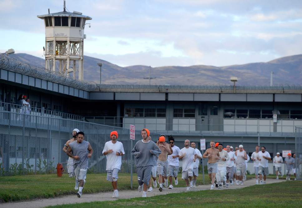 Al Hartmann  |  The Salt Lake Tribune Inmates at the Utah State Prison-Draper run the enclosed excercise yard-track at the start of the Draper Invitational Marathon, Half-Marathon and 10K races Tuesday morning October 25.  110 times around the track for the full marathon.
