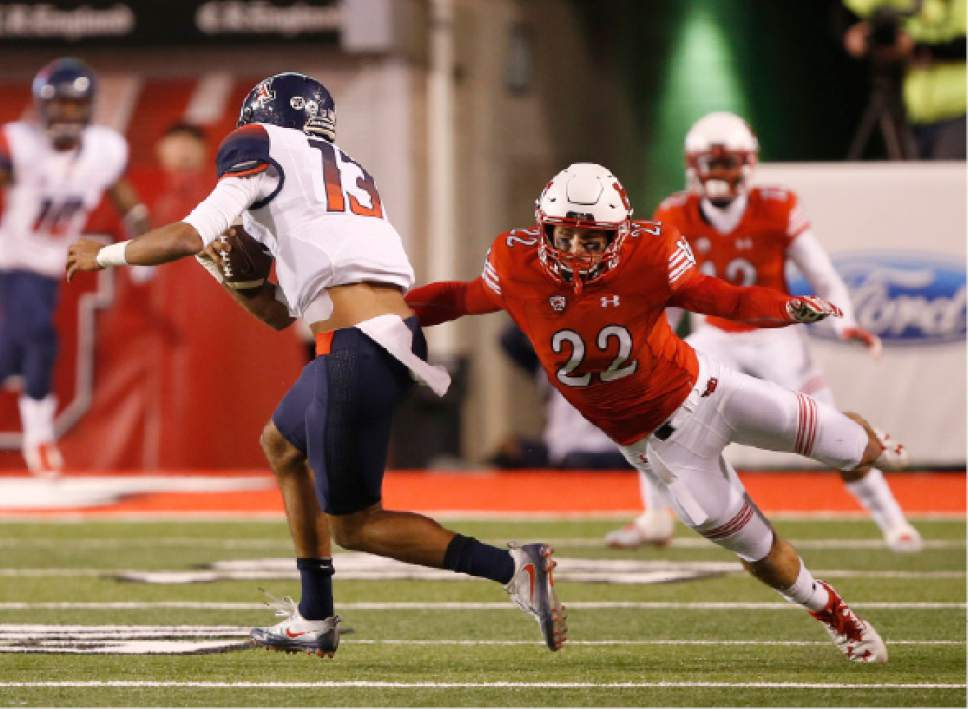 Arizona quarterback Brandon Dawkins (13) runs out of the tackle of Utah defensive back Chase Hansen (22) during the first half of an NCAA college football game, Saturday, Oct. 8, 2016, in Salt Lake City. (AP Photo/George Frey)