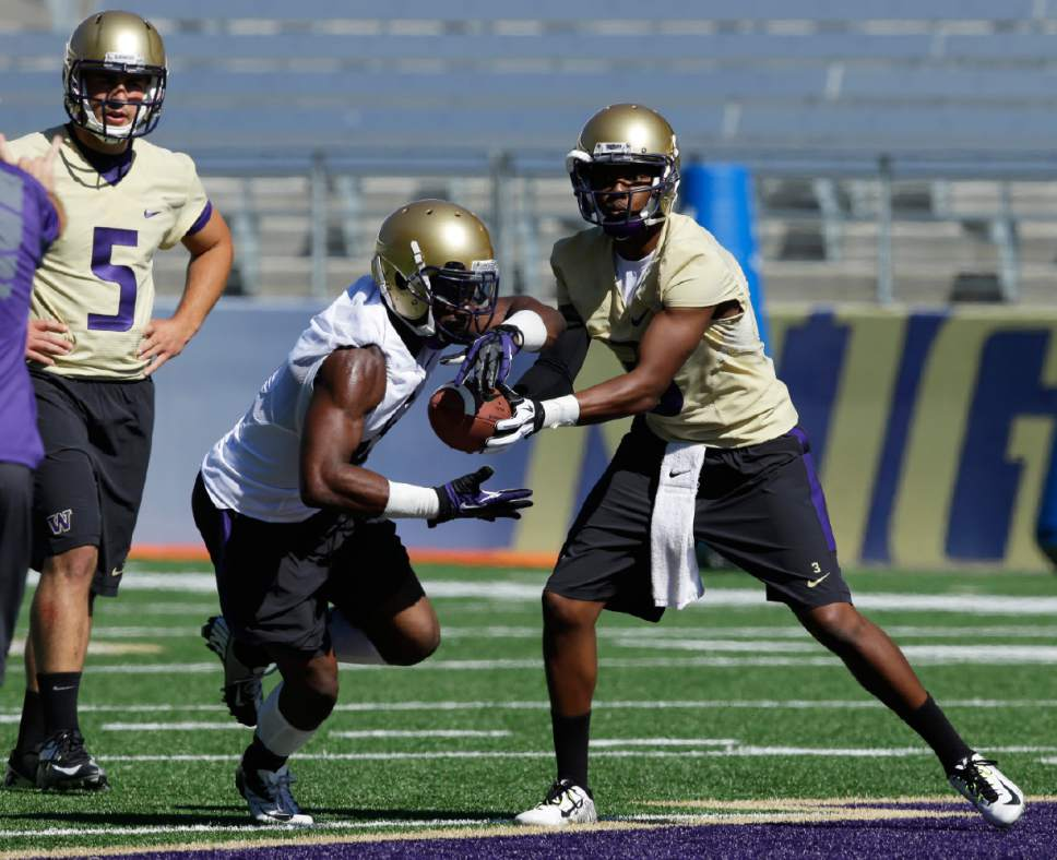 Washington quarterback Troy Williams, right, hands off to tailback Deontae Cooper, center, as quarterback Jeff Lindquist looks on at left, during the first session of NCAA college football practice before the upcoming fall season, Monday, Aug. 4, 2014, in Seattle. (AP Photo/Ted S. Warren)