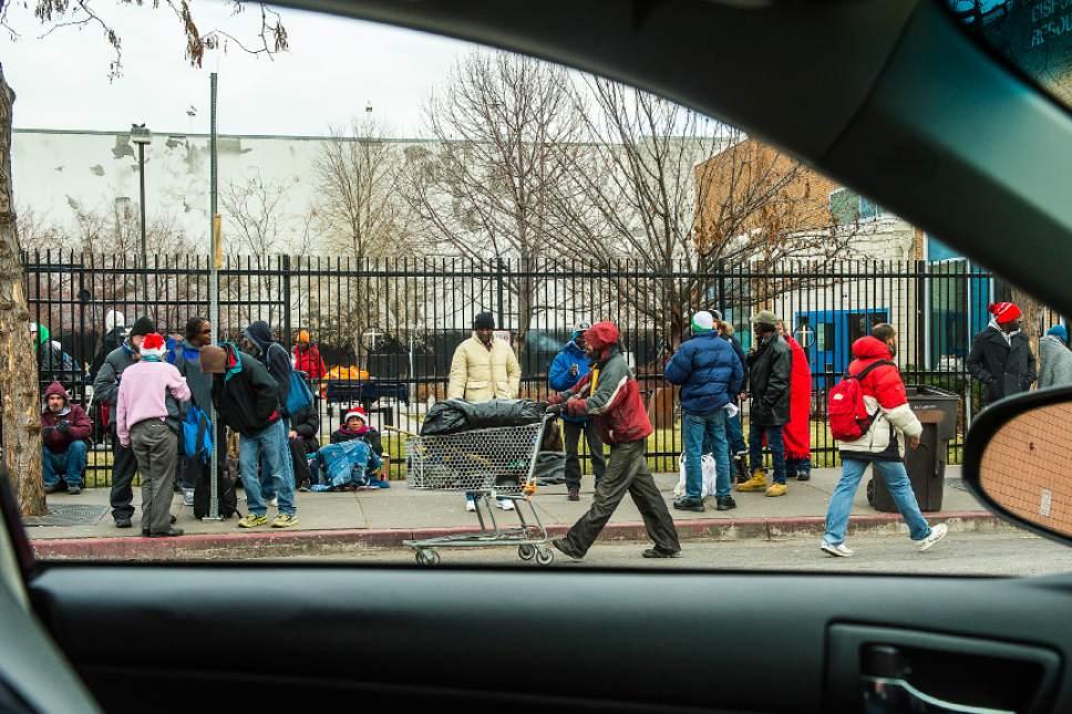Chris Detrick  | Tribune file photo Homeless men and women wait outside the Catholic Community Services of Utah in December 2014.
