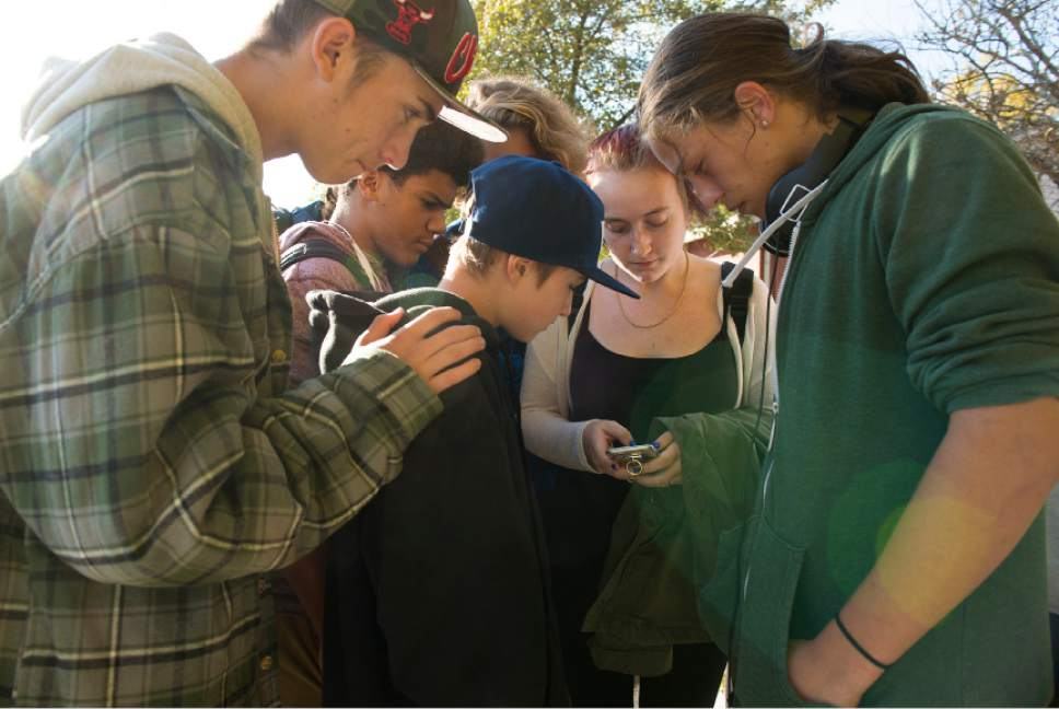 Leah Hogsten  |  The Salt Lake Tribune Kalani Matthews, 17, right, and his friends gather around Rachel Otteson, 18, as they try to identify the Union Middle School shooting suspect in photographs. A 16-year-old boy was critically injured after being shot outside Union Middle School in Sandy by a 14-year-old, who is a student at the middle school. The shooting occurred about 3 p.m. when two teenage boys got into an argument on a field north of the school, said Sandy police Sgt. Dean Carriger. The victim -- who is a student at Hillcrest High School -- was transported by ambulance in critical condition to Intermountain Medical Center, where he went into surgery about 4:30 p.m. to treat two gunshot wounds. The 14-year-old suspect is in custody.