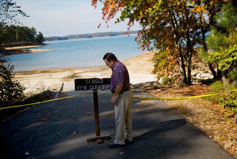 In this Wednesday, Oct. 26, 2016 photo, U.S. Army Corps of Engineers Natural Resources Manager Nick Baggett fixes a sign posted at a closed off boat ramp where the Lake Lanier shoreline has receded in Flowery Branch, Ga. Some of the South's most beautiful mountains and valleys this fall are filled with desperation, as a worsening drought kills crops, threatens cattle and sinks lakes to their lowest levels in years. (AP Photo/David Goldman)