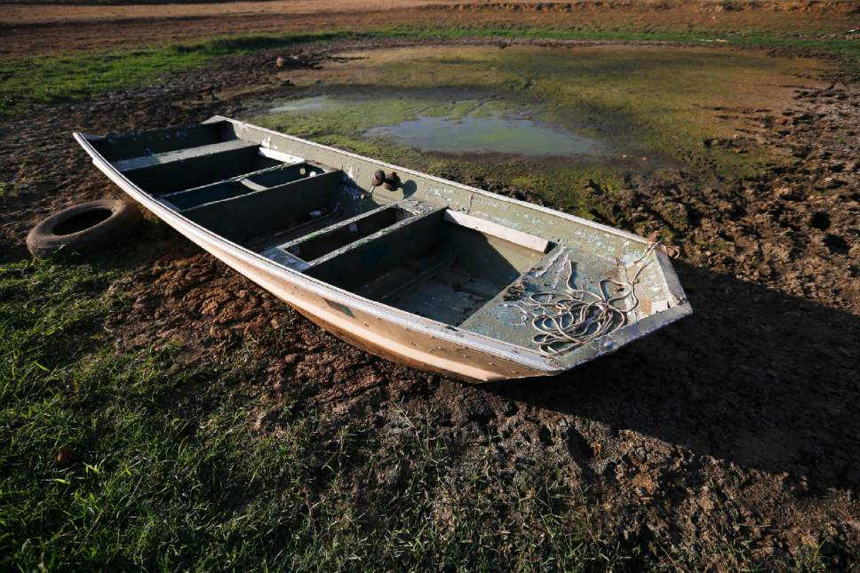 In this Wednesday, Oct. 26, 2016 photo, an abandoned boat sits in the remains of a dried out pond  in Dawson, Ala. Some of the South's most beautiful mountains and valleys are filling with desperation as a worsening drought kills crops, threatens cattle and sinks lakes to their lowest levels in years. The very worst conditions are in the mountains of northern Alabama and Georgia.  (AP Photo/Brynn Anderson)