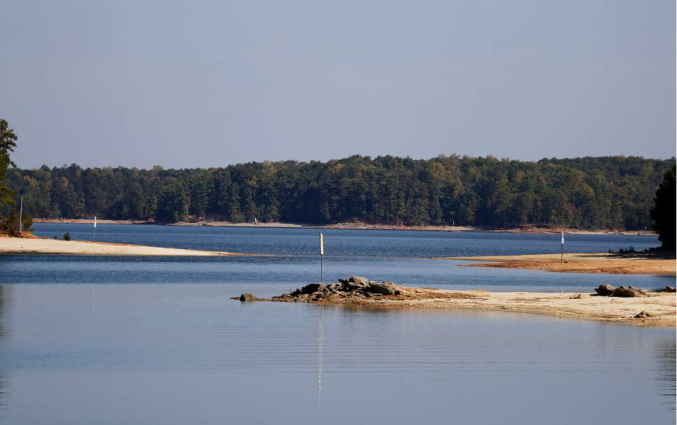 In this Wednesday, Oct. 26, 2016 photo, buoys warning boaters of underwater hazards sit exposed as Lake Lanier water levels recede about eight feet below normal in Buford, Ga. Some of the South's most beautiful mountains and valleys this fall are filled with desperation, as a worsening drought kills crops, threatens cattle and sinks lakes to their lowest levels in years. (AP Photo/David Goldman)