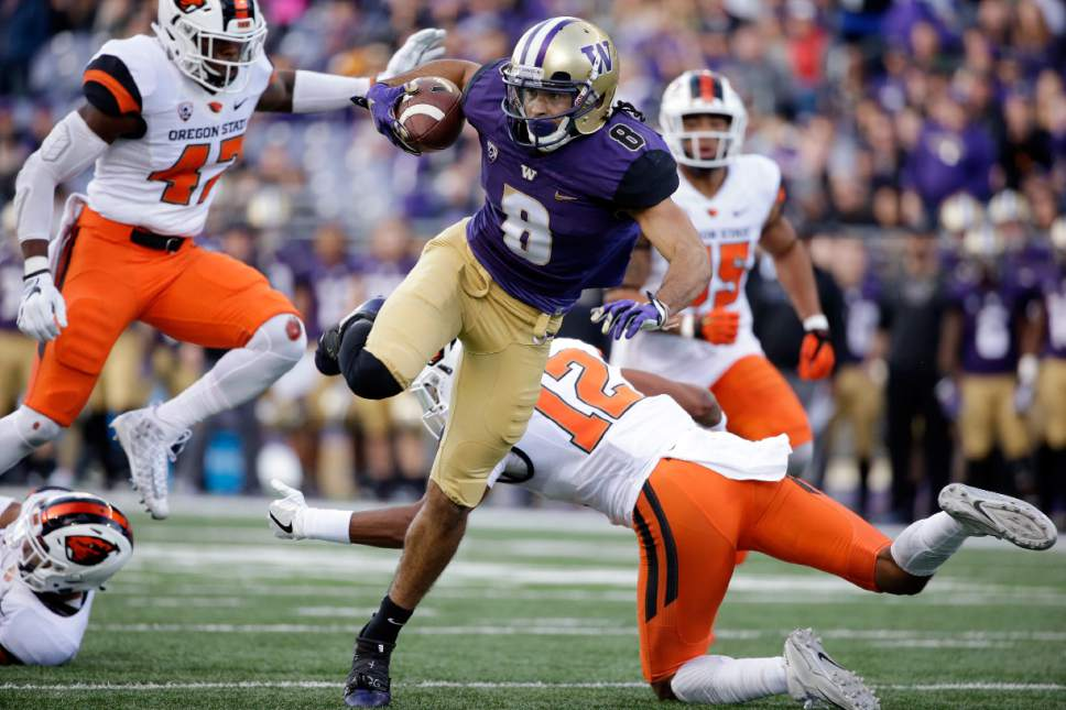Washington's Dante Pettis (8) twists to avoid Oregon State defenders as he scores on a 23-yard pass reception in the first half of an NCAA college football game Saturday, Oct. 22, 2016, in Seattle. (AP Photo/Elaine Thompson)