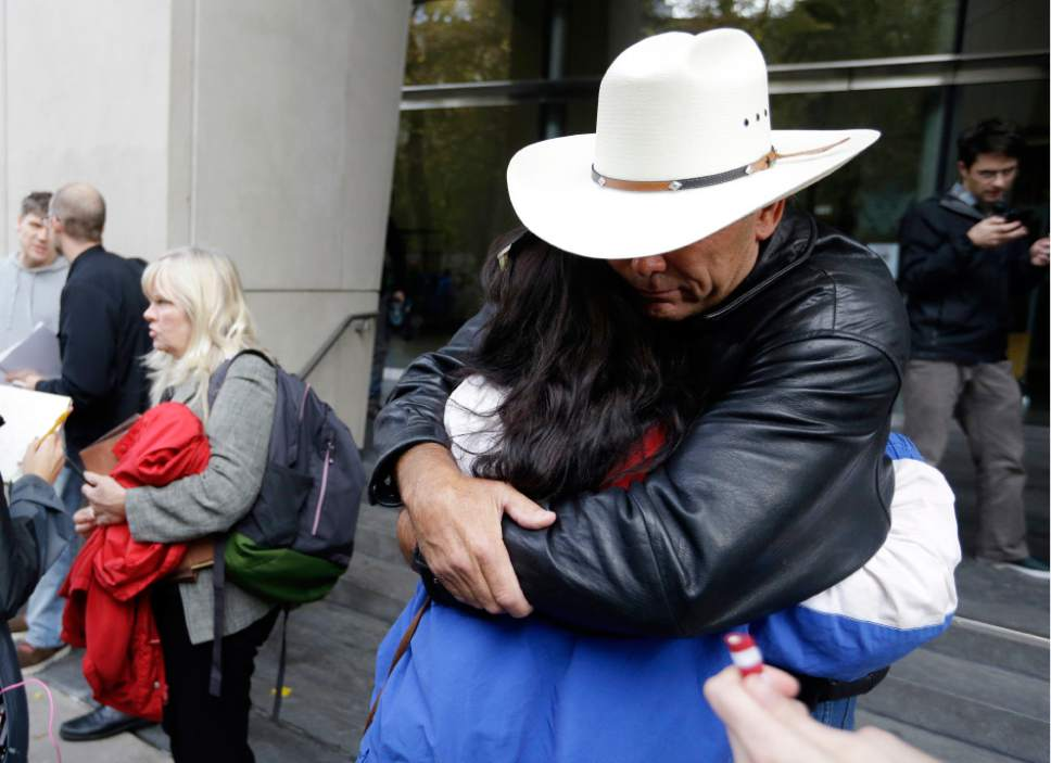 Defendant Shawna Cox speaks at left as supporters hug outside federal court in Portland, Ore., Thursday, Oct. 27, 2016. A jury exonerated brothers Ammon and Ryan Bundy and five others of conspiring to impede federal workers from their jobs at the Malheur National Wildlife Refuge. (AP Photo/Don Ryan)