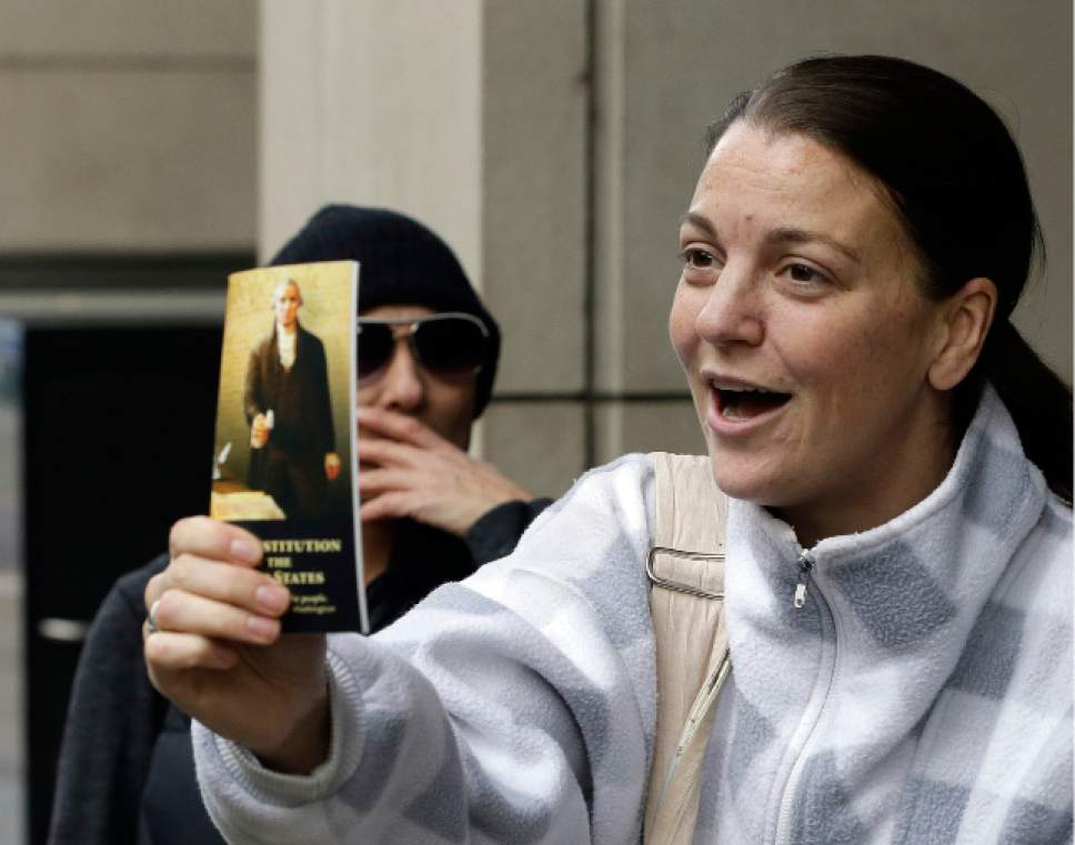 A supporter holds out a copy of the constitution after hearing a verdict outside federal court in Portland, Ore., Thursday, Oct. 27, 2016. A jury exonerated brothers Ammon and Ryan Bundy and five others of conspiring to impede federal workers from their jobs at the Malheur National Wildlife Refuge. (AP Photo/Don Ryan)