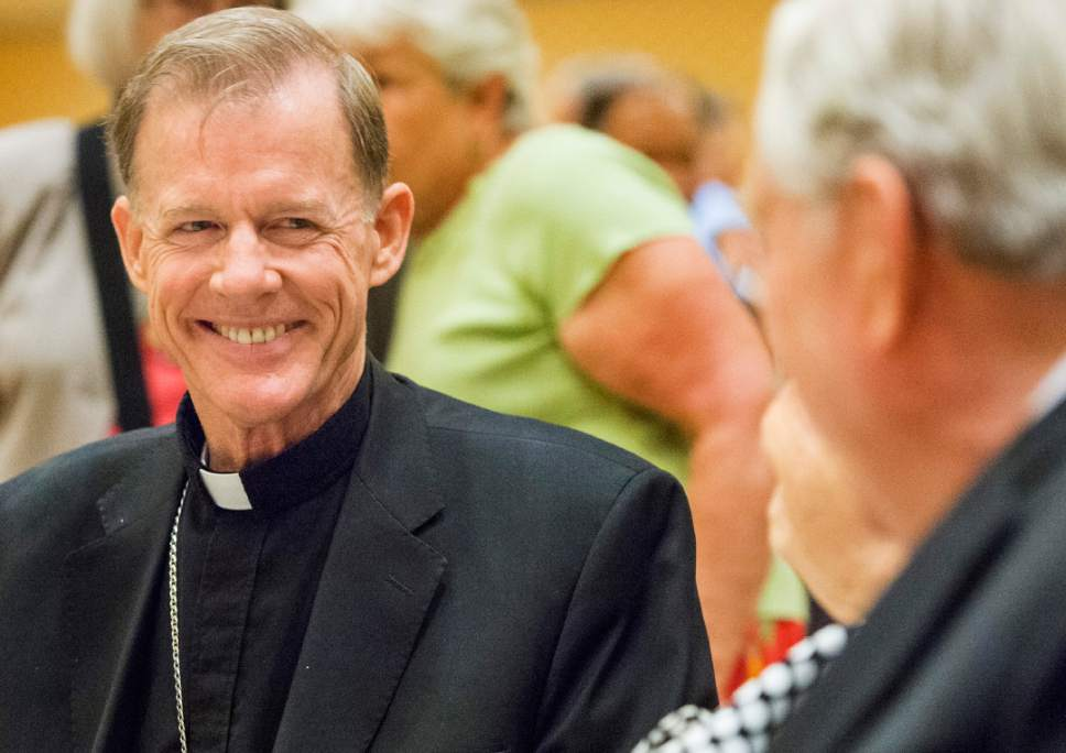 Rick Egan  |  The Salt Lake Tribune  Departing Archbishop John C. Wester smiles as he visits with Barbara and LDS apostle M Russell Ballard  at a reception at the Little America on Sunday, May 31, 2015.