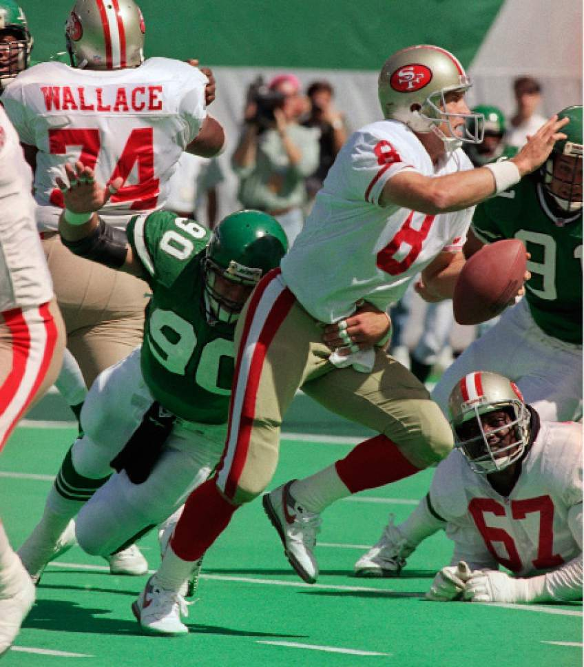 FILE - In this Sept. 20, 1992, file photo, New York Jets defensive end Dennis Byrd puts pressure on San Francisco 49ers quarterback Steve Young during an NFL football game in East Rutherford, N.J. Byrd, the former NFL defensive lineman whose career was ended by neck injury, was killed Saturday, Oct. 15, 2016, in a car crash in Oklahoma. He was 51. (AP Photo/Bob Strong, File)