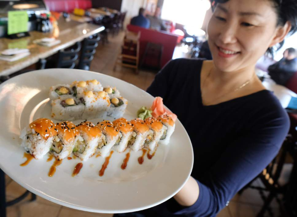 Francisco Kjolseth  |  The Salt Lake Tribune Jungsoo Oh, co-owner of Hanabi Sushi in Midvale, shows off a sushi order for customers during a recent lunch visit.