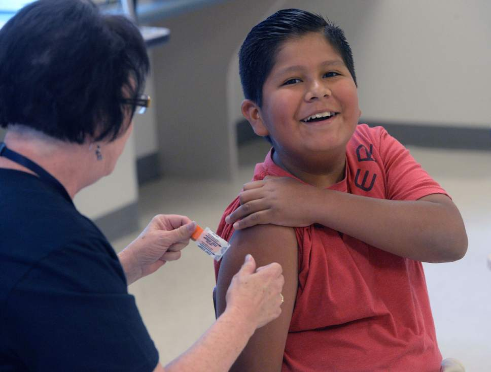 Al Hartmann  |  The Salt Lake Tribune  Alexis Herrera, 11, cracks a smile after getting an immunization shot for school at the Junior League CARE Fair in the Horizonte Center in Salt Lake City in July. It's Utah's largest free health fair, requiring no appointments or insurance for services such as immunizations, vision, hearing and speech screenings and dental exams. The number of uninsured Utah children dropped to 65,000 in 2015, but the state still ranks poorly compared to others across the country, according to a recent report.