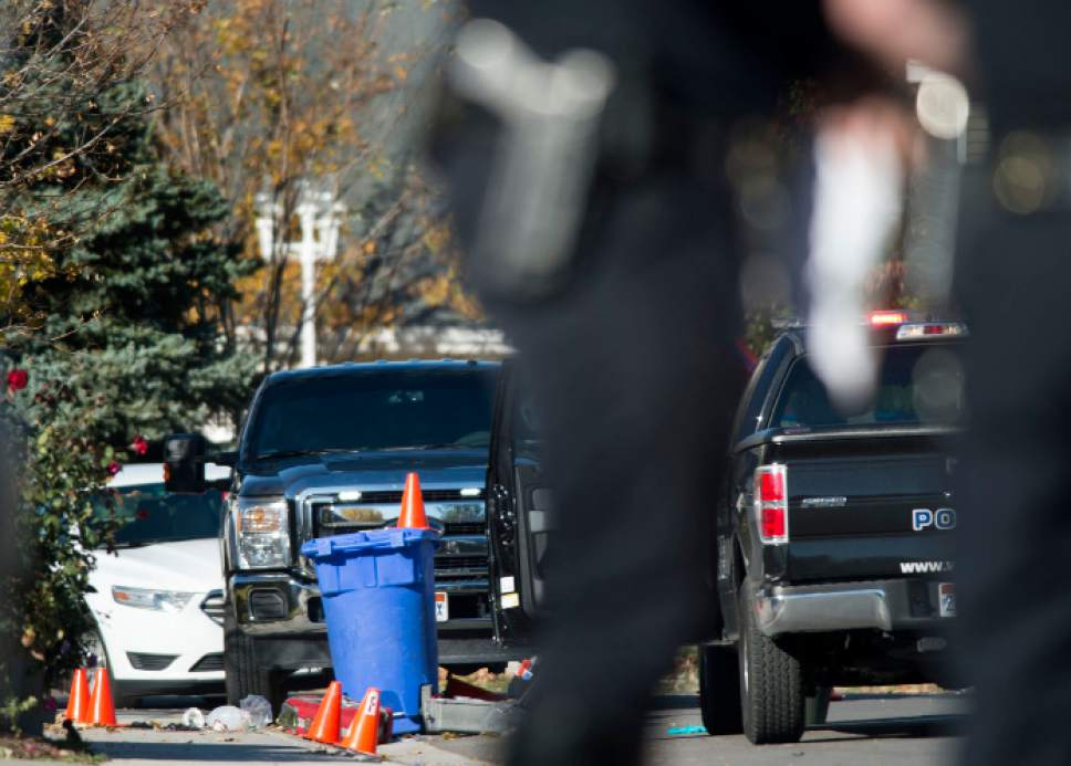 Steve Griffin / The Salt Lake Tribune   Police investigate a crime scene after a bank robbery suspect was critically injured in a shoot-out with police in West Jordan, after crashing his truck into a cinderblock wall, following a robbery and high speed chase at a local credit police reported in West Jordan, Utah Wednesday November, 02, 2016.