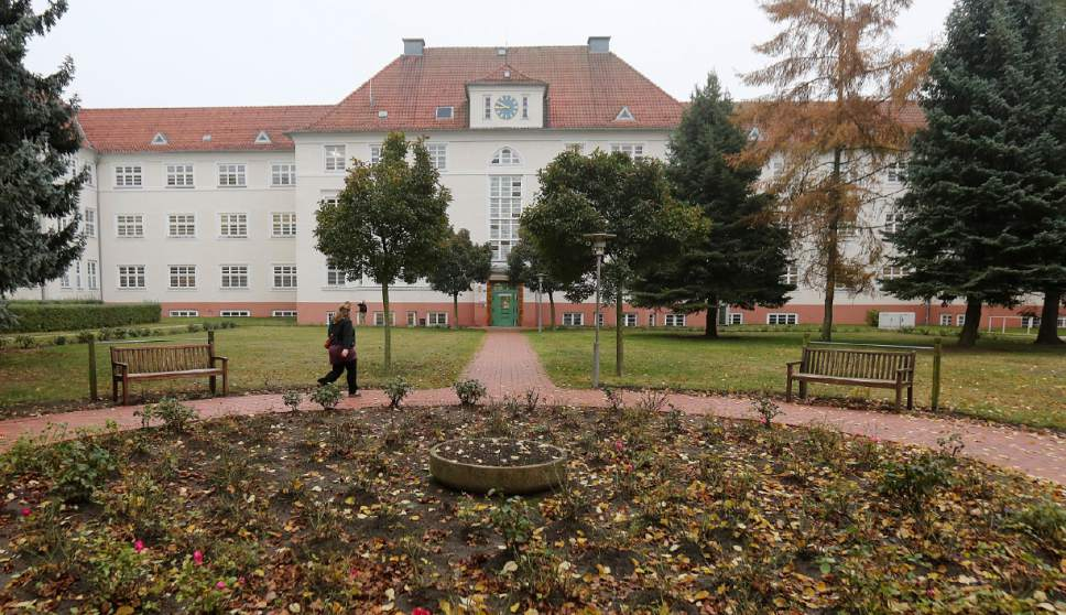 In this photo Oct. 27, 2016 photo a woman walks in front of the city hospital in Prenzlau, Germany. Up to 20 women from Poland come to the hospital every week to terminate pregnancy because Poland's law, one of the most restrictive in Europe, bans abortion except for cases when the woman's health or life is in danger, the pregnancy results from crime like rape or the fetus is incurably damaged.  (AP Photo/Czarek Sokolowski)