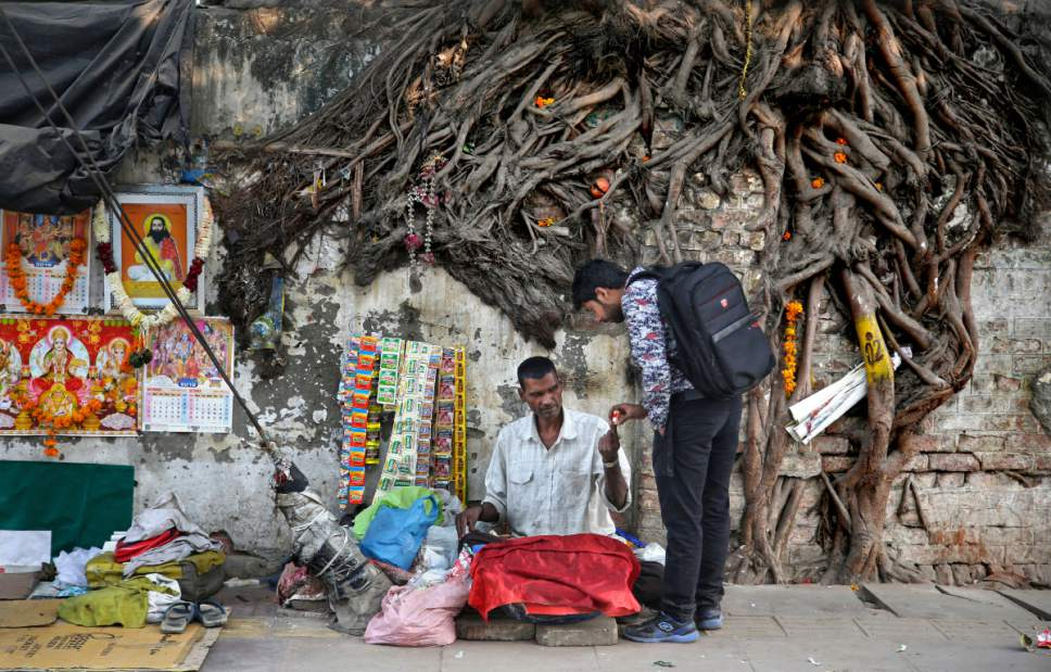In this Wednesday, Nov. 2, 2016 photo, an Indian man buys a packet of cigarette from a roadside vendor in New Delhi, India. Despite harsh laws passed more than a decade ago banning smoking in public and sales to children, smoking is still common across the country. A government survey in 2010 showed nearly 35 percent of adults were either smoking or chewing tobacco. (AP Photo/Altaf Qadri)