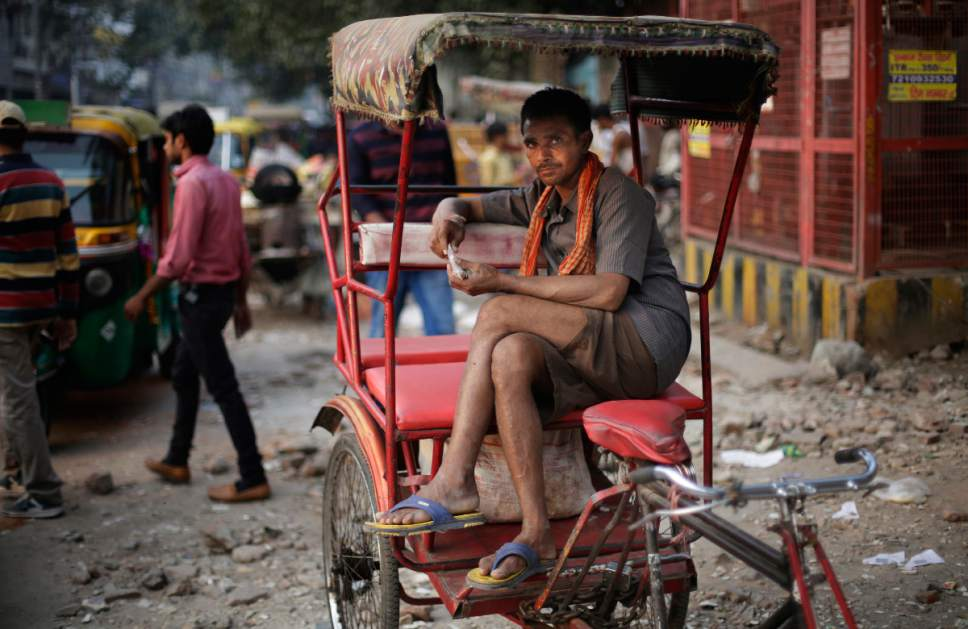 In this Wednesday, Nov. 2, 2016 photo, an Indian rickshaw puller prepares chewable tobacco in New Delhi, India. Despite harsh laws passed more than a decade ago banning smoking in public and sales to children, smoking is still common across the country. A government survey in 2010 showed nearly 35 percent of adults were either smoking or chewing tobacco. (AP Photo/Altaf Qadri)