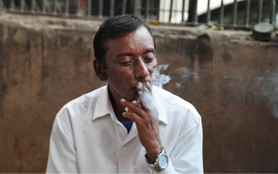 In this Thursday, Nov. 3, 2016 photo, an Indian man smokes a cigarette in New Delhi, India. Despite harsh laws passed more than a decade ago banning smoking in public and sales to children, smoking is still common across the country. A government survey in 2010 showed nearly 35 percent of adults were either smoking or chewing tobacco. (AP Photo/Altaf Qadri)