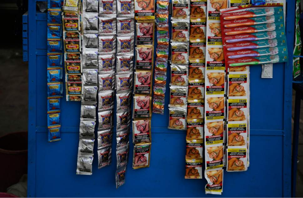 In this Wednesday, Nov. 2, 2016 photo, packets of various tobacco products hang from a kiosk in New Delhi, India. India wants scary photos of rotting lungs and mouth tumors covering packets sold in the country. Putting pictorial warnings on cigarette packets is an attempt to educate people about the risks. Still, national drives to discourage smoking and cut back tobacco sales haven't done enough, campaigners say. Smoking-related deaths are still rising worldwide, with 80 percent of them expected to occur in developing country populations by 2030. (AP Photo/Altaf Qadri)