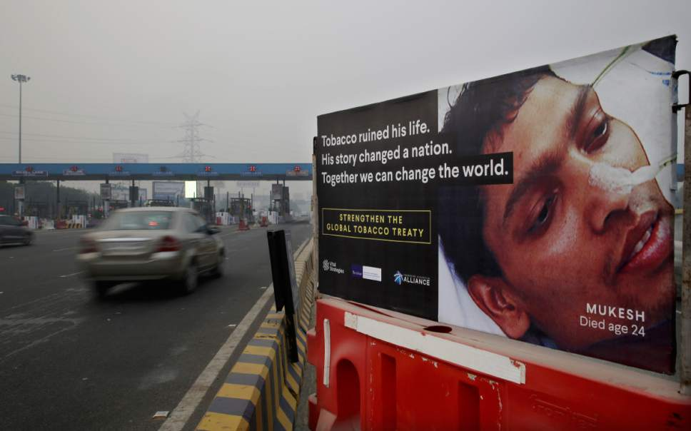 In this Friday, Nov. 4, 2016 photo, an anti-tobacco warning is erected on a road divider on the outskirts of New Delhi, India. India wants scary photos of rotting lungs and mouth tumors covering packets sold in the country. Putting pictorial warnings on cigarette packets is an attempt to educate people about the risks. Still, national drives to discourage smoking and cut back tobacco sales haven't done enough, campaigners say. Smoking-related deaths are still rising worldwide, with 80 percent of them expected to occur in developing country populations by 2030. (AP Photo/Altaf Qadri)