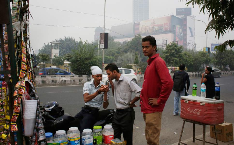In this Friday, Nov. 4, 2016 photo, Indians share a smoke in front of a roadside kiosk on the outskirts of New Delhi, India. More than 1 million Indians die each year from tobacco-related diseases that cost the country some $16 billion annually, according to the World Health Organization. (AP Photo/Altaf Qadri)