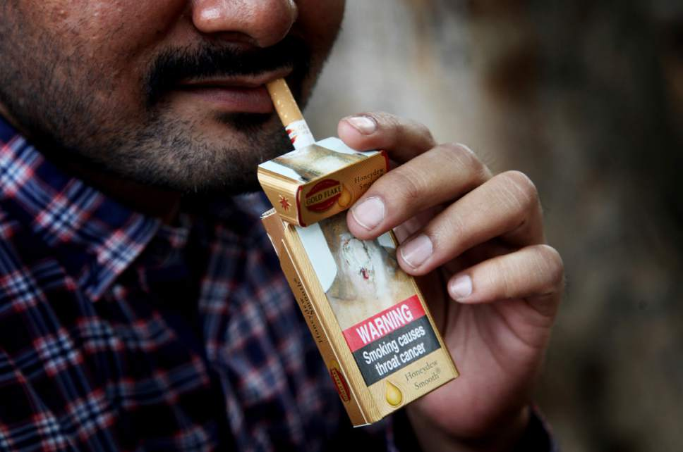 In this Wednesday, Nov. 2, 2016 photo, an Indian man takes a cigarette from a pack in New Delhi, India. India wants scary photos of rotting lungs and mouth tumors covering packets sold in the country. Putting pictorial warnings on cigarette packets is an attempt to educate people about the risks. Still, national drives to discourage smoking and cut back tobacco sales haven't done enough, campaigners say. Smoking-related deaths are still rising worldwide, with 80 percent of them expected to occur in developing country populations by 2030. (AP Photo/Altaf Qadri)