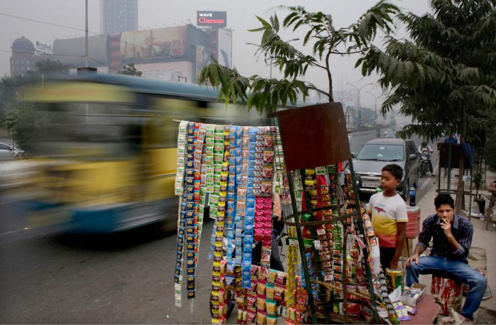 In this Friday, Nov. 4, 2016 photo, an Indian man smokes a cigarette sitting next to a roadside vendor selling tobacco products on the outskirts of New Delhi, India. Starting Monday, representatives from at least 178 countries are meeting for five days in the Indian capital to discuss how they can further the fight against smoking and push back against tobacco company lobbyists. (AP Photo/Altaf Qadri)