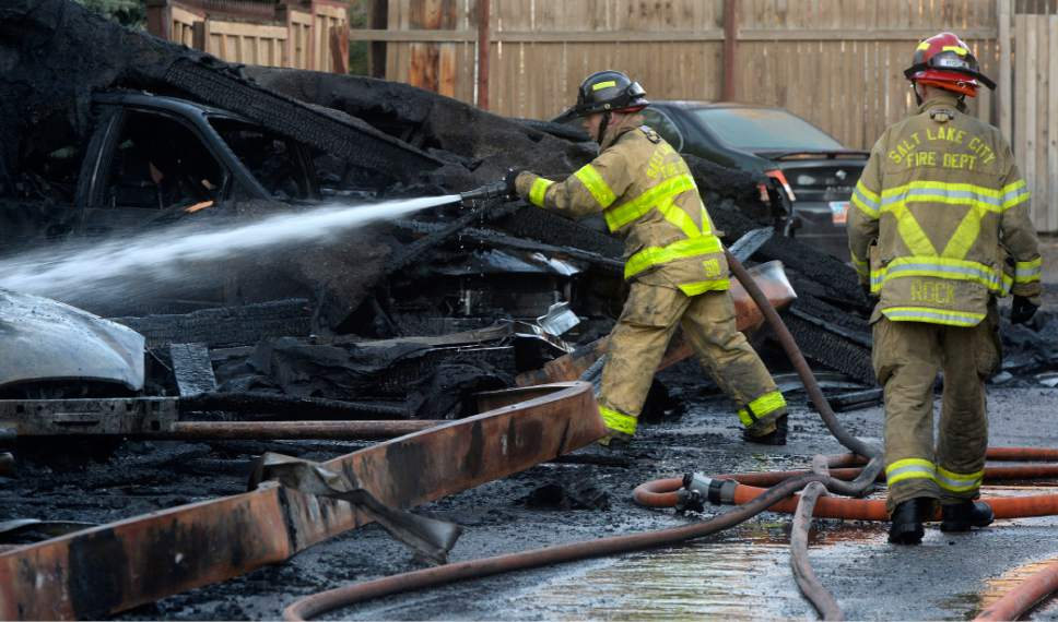 Al Hartmann     The Salt Lake Tribune Salt Lake City Fire Department finishes putting out a fire at 825 East 600 South Monday Nov. 7, 2016.  The fire burned 16 cars in a carport and singed the outside of the building apartment complex.