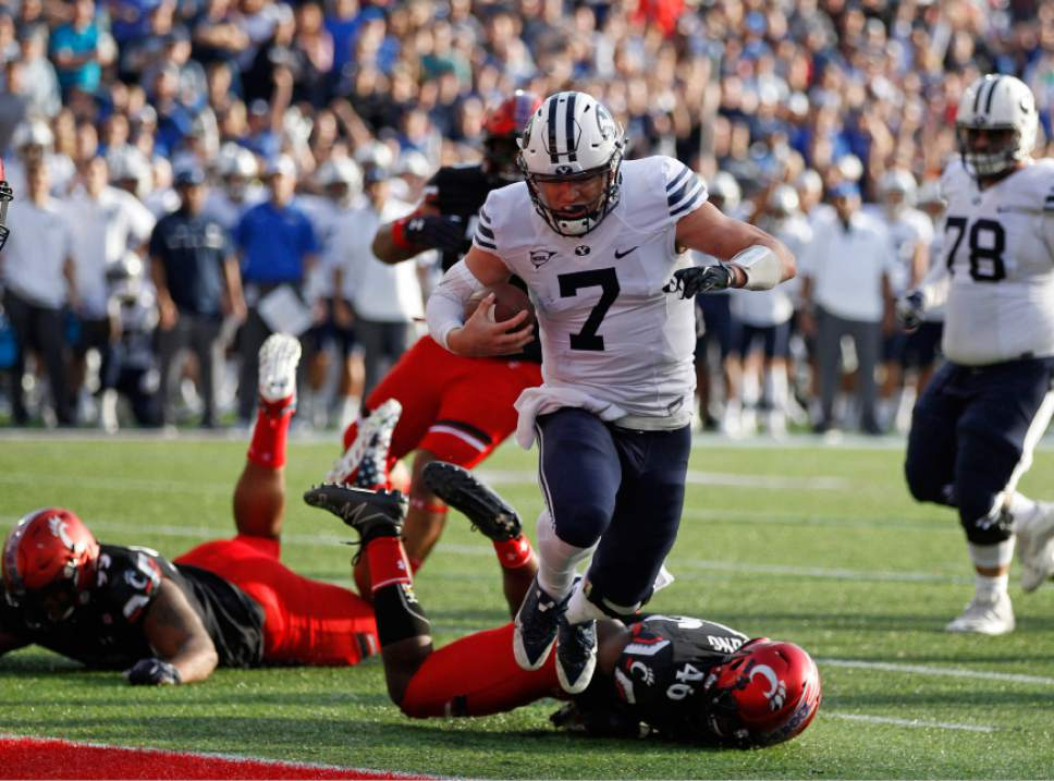 Brigham Young quarterback Taysom Hill (7) scores a touch down in front of Cincinnati defensive back Perry Young (46) during the first half of an NCAA college football game, Saturday, Nov. 5, 2016, in Cincinnati. (AP Photo/Gary Landers)