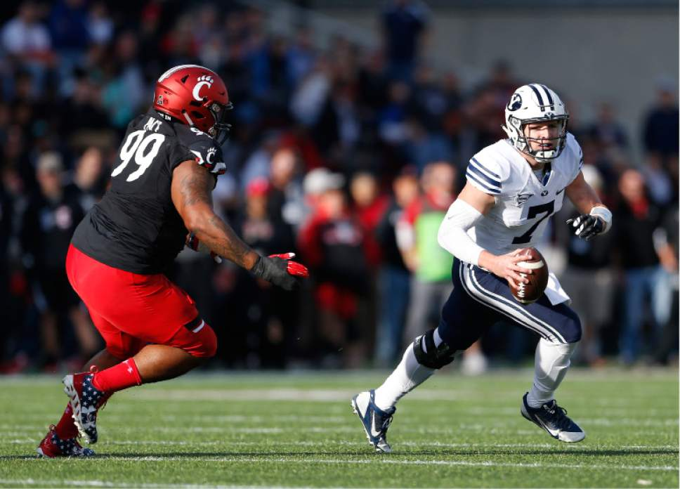 Brigham Young quarterback Taysom Hill (7) scrambles away from Cincinnati defensive tackle Alex Pace (99) during the first half of an NCAA college football game, Saturday, Nov. 5, 2016, in Cincinnati. (AP Photo/Gary Landers)