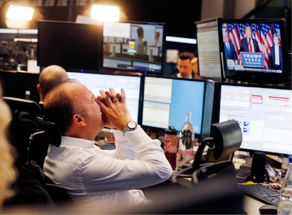 A broker reacts as new elected U.S. President Donald Trump shows up on a television screen at the stock market in Frankfurt, Germany, Wednesday, Nov. 9, 2016. (AP Photo/Michael Probst)