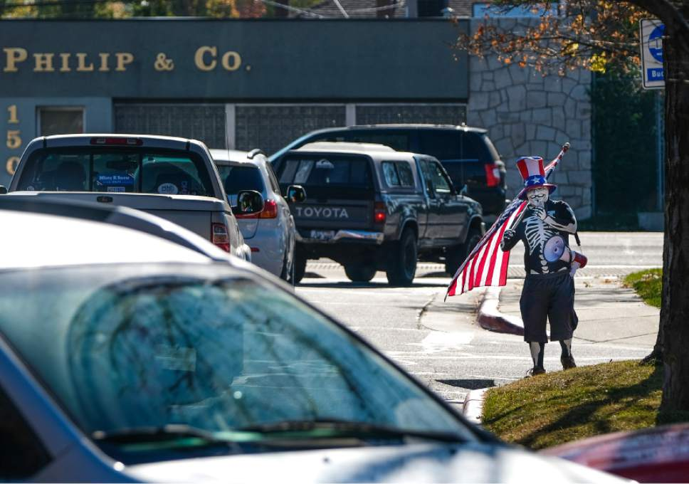 "Francisco Kjolseth | The Salt Lake Tribune With a mask a flag and a bullhorn an individual who didn't want to give his name says ""I'm just and Anarchist. I don't support anything. I think the whole thing is rigged"" as he walks the grounds near the Salt Lake County complex on  Tuesday, Nov. 8, 2016, after police asked him to move away from the election process."