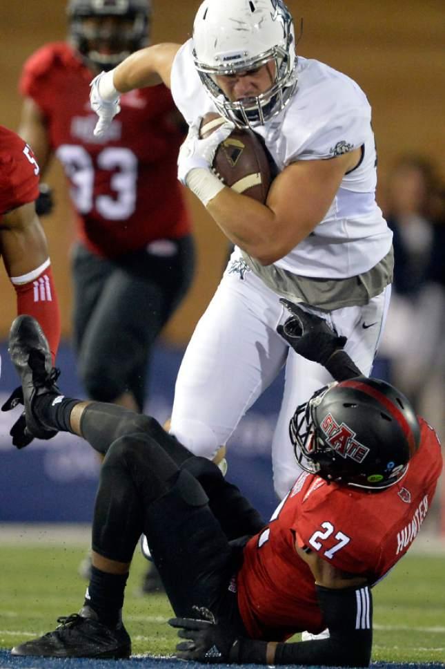 Chris Detrick  |  The Salt Lake Tribune Utah State Aggies tight end Wyatt Houston (83) runs through Arkansas State Red Wolves defensive back Money Hunter (27) during the game at Maverik Stadium Friday September 16, 2016.