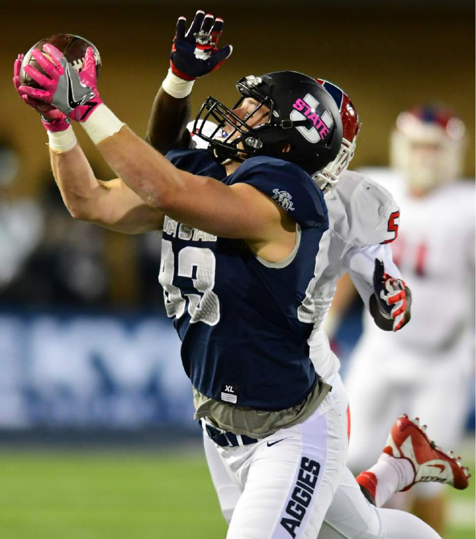 Utah State's Wyatt Houston makes a catch as Fresno State's Dalen Jones defends during an NCAA college football game, Saturday, Oct. 22, 2016, in Logan, Utah. (John Zsiray/Herald Journal via AP)