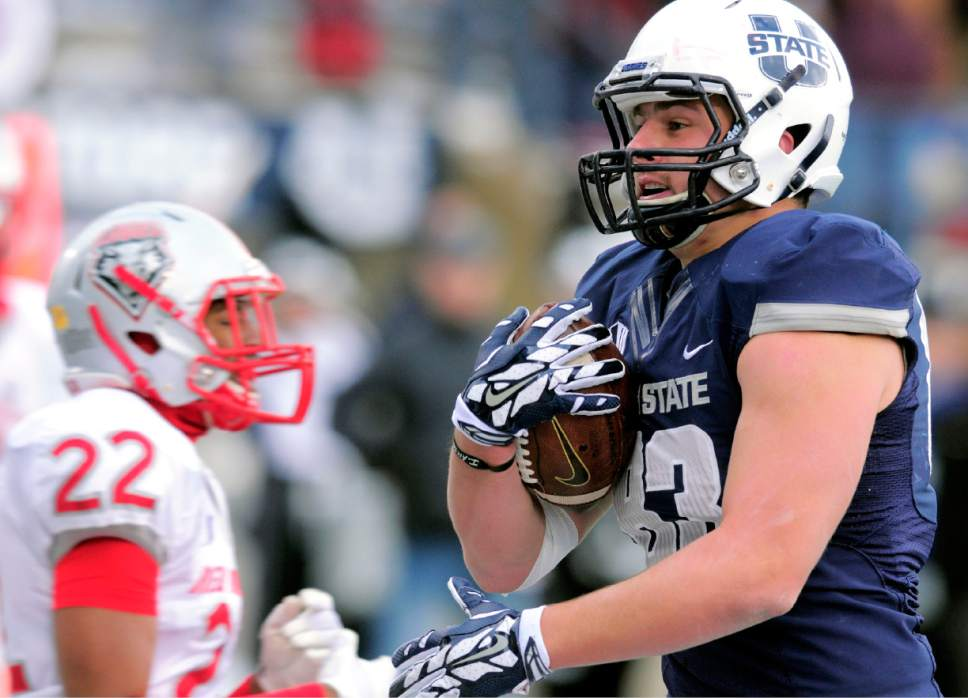 Utah State tight end Wyatt Houston catches a touchdown pass as New Mexico defensive back Markel Byrd (22) defends during an NCAA college football game, Saturday, Nov. 15, 2014, in Logan, Utah. (AP Photo/The Herald Journal, Eli Lucero)
