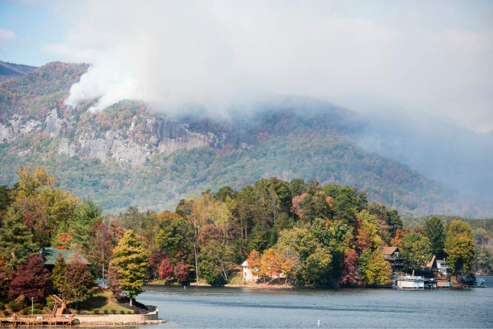 Smoke from the Party Rock fire near Lake Lure spreads as emergency services and the N.C. Forest Service work to contain the blaze Wednesday Nov. 9, 2016 at Lake Lure, N.C.  Unseasonably warm dry weather has deepened a drought that's igniting forest fires across the southeastern U.S.   (Abigail Margulis/The Asheville Citizen-Times via AP)