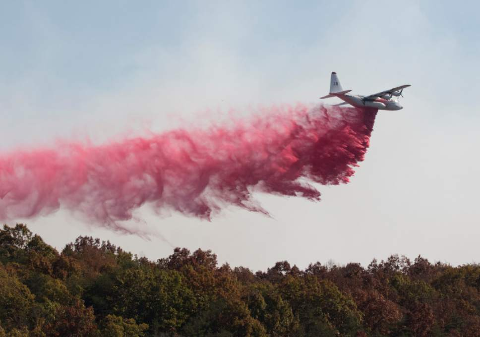 An aircraft from the US Forestry Service drops fire retardant on a wildfire burning along the Flipper Bend area of Signal Mountain in Hamilton County, Tenn., on Wednesday, Nov. 9, 2016. Wildfires burning across the South have created a smoky haze over metro Atlanta and prompted a public health advisory in Kentucky, and the forests are expected to continue burning for days as flaming leaves fall to the ground and spread the flames. Other fires were burning in parts of Alabama, North Carolina and Tennessee. (Dan Henry/The Chattanooga Times Free Press via AP)