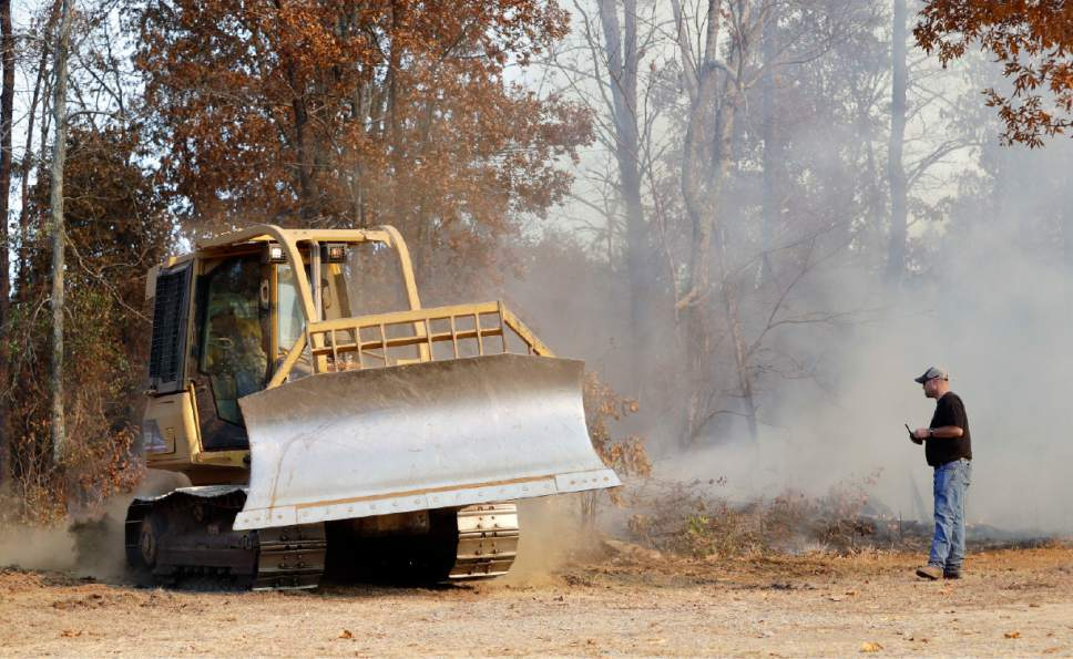 Assistant Chief Dusten Woodard, right, of the Mowbray Volunteer Fire Depart, watches a crew dig a fire break fighting a wildfire Thursday, Nov. 10, 2016, in Soddy-Daisy, Tenn. Federal authorities say warmer-than-average temperatures and no rainfall are deepening a drought that's sparking forest fires across the Southeastern U.S. (AP Photo/Mark Humphrey)