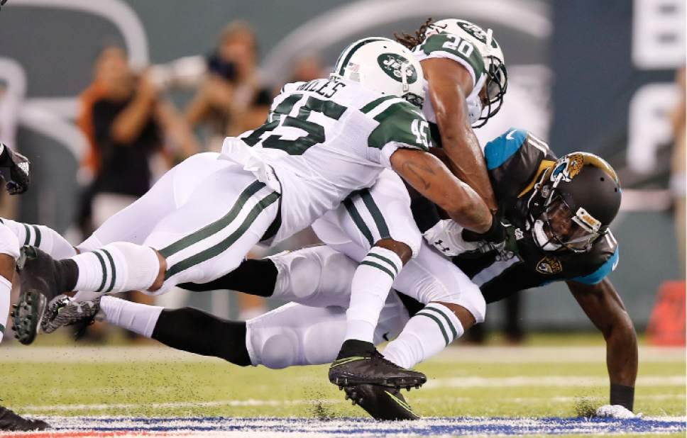 FILE - In this Aug. 11, 2016 file photo, New York Jets strong safety Rontez Miles (45) and cornerback Marcus Williams (20) tackle Jacksonville Jaguars wide receiver Marqise Lee (11) during the second quarter of an NFL football game, in East Rutherford, N.J. (AP Photo/Kathy Willens)