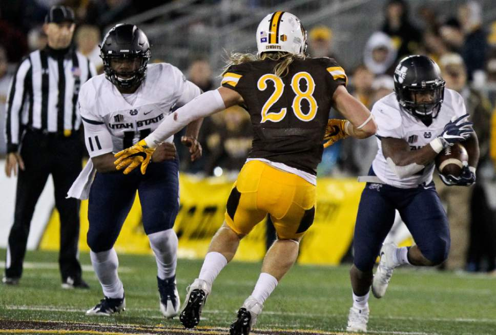 Utah State running back Tonny Lindsey avoids a tackle from Wyoming's Andrew Wingard during the second half of an NCAA college football game in Laramie, Wyo., Saturday, Nov. 5, 2016. (AP Photo/Shannon Broderick)