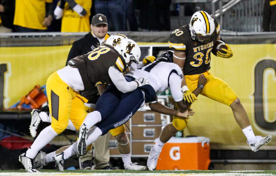 Utah State quarterback Damion Hobbs attempts to tackle Wyoming linebacker Logan Wilson as he runs down the field with the ball during the second half of an NCAA college football game in Laramie, Wyo., Saturday, Nov. 5, 2016. (AP Photo/Shannon Broderick)