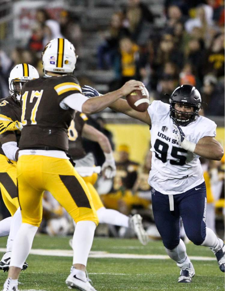 Utah State defensive end Ricky Ali'ifua runs towards Wyoming quarterback Josh Allen during the second half of an NCAA college football game in Laramie, Wyo., Saturday, Nov. 5, 2016. (AP Photo/Shannon Broderick)
